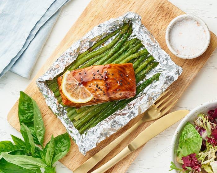 Paquete de papel de aluminio con pescado rojo. Filete de salmón con espárragos. Cena caliente al horno