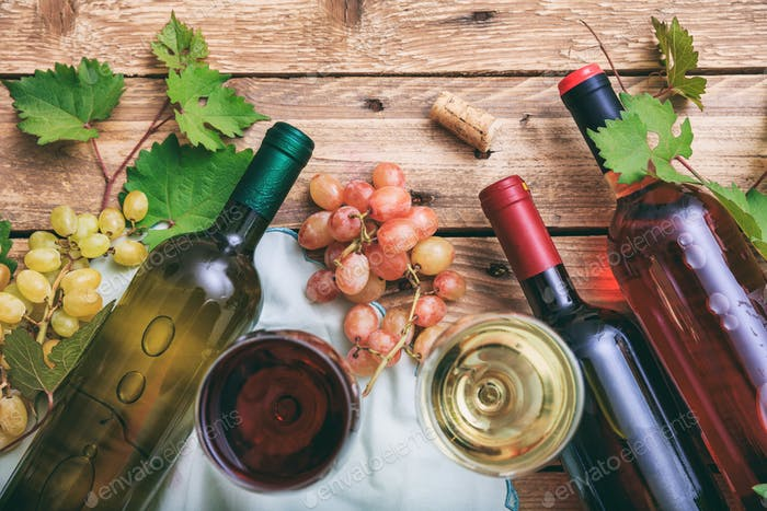 Red and white wine glasses and bottles on wooden background. Fresh grapes and grape leaves