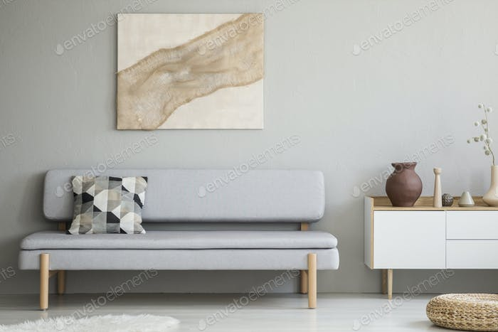 Painting on grey wall above settee with cushion in modern living