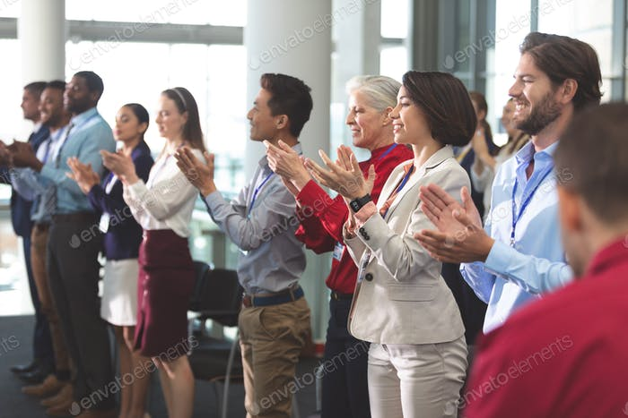 Business people applauding standing in business seminar in office building