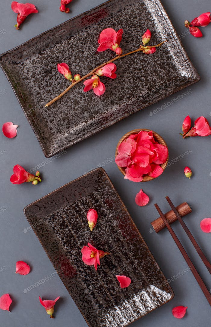 Chopsticks, rectangular plates and pink flowers on gray background