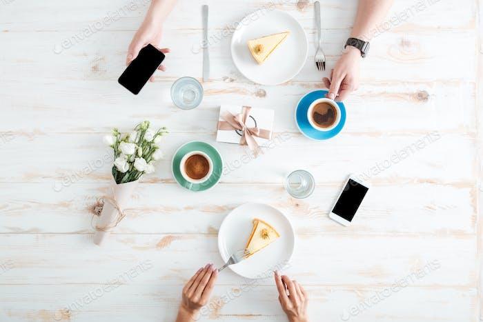 Hände von Paaren essen Kuchen und mit Smartphones auf dem Tisch
