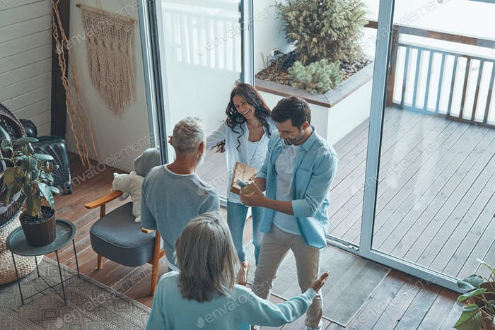 Top view of happy senior parents meeting young couple inside the house