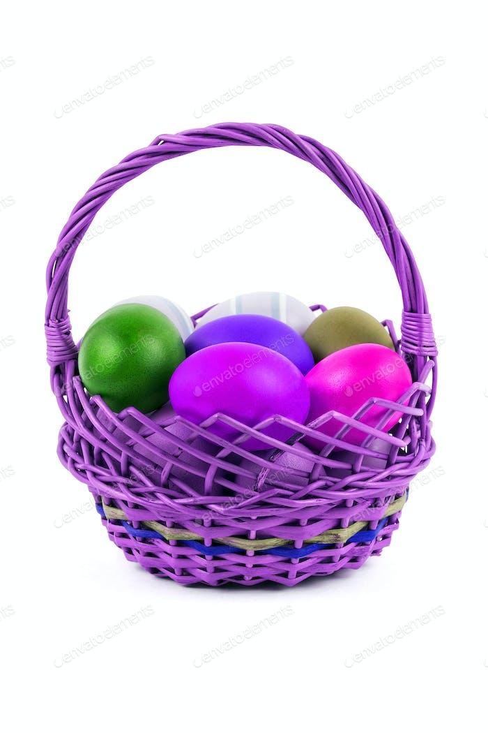 Huevos de Pascua en una cesta sobre un Fondo blanco