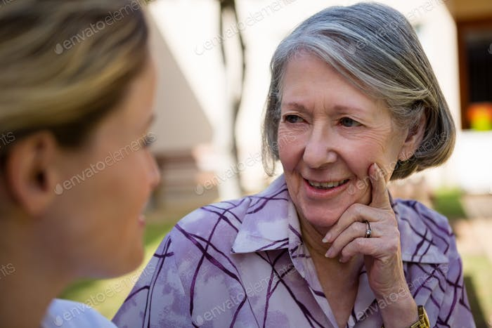 Senior woman talking to doctor at yard