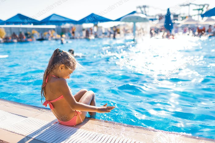 A lovely little girl sits on the side of the pool with her feet in the water enjoying the sun
