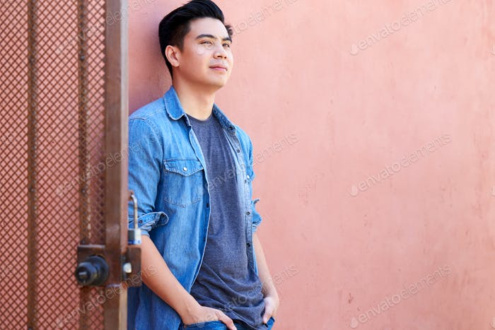 Outdoor-Porträt von Junger Mann Auf der Straße Lehnt sich an die Wand