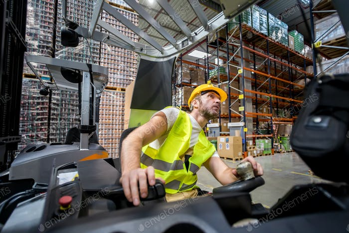 Warehouse worker in a forklift truck places the packages on the shelves