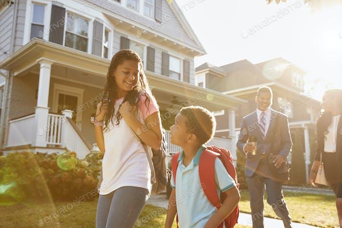Businesswoman Parents Walking Children To School On Way To Work