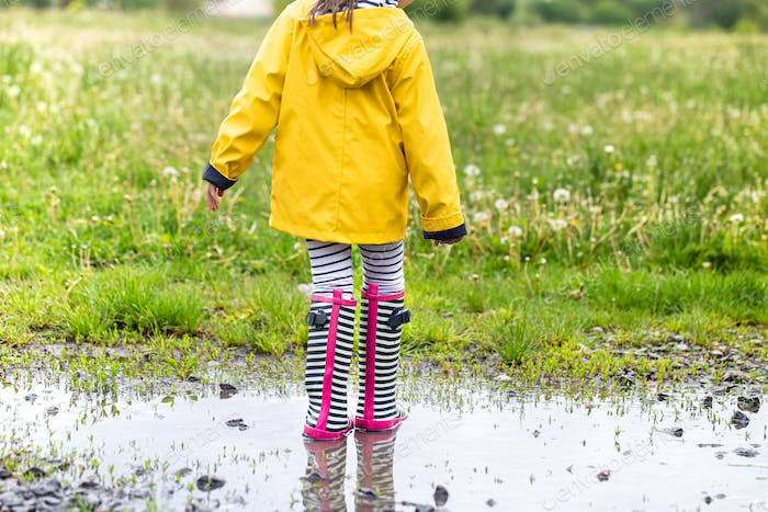 A child in rubber boots jumps in a puddle.