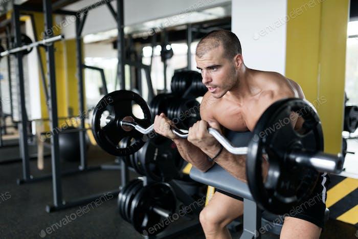 Athlete muscular bodybuilder in gym training biceps