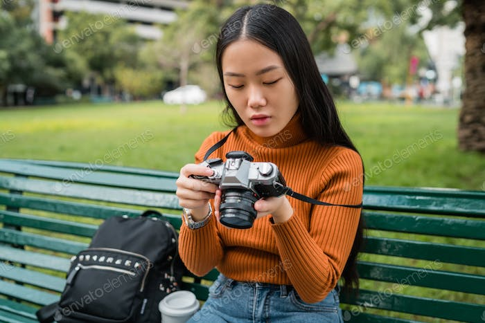 Asian woman using a professional camera.