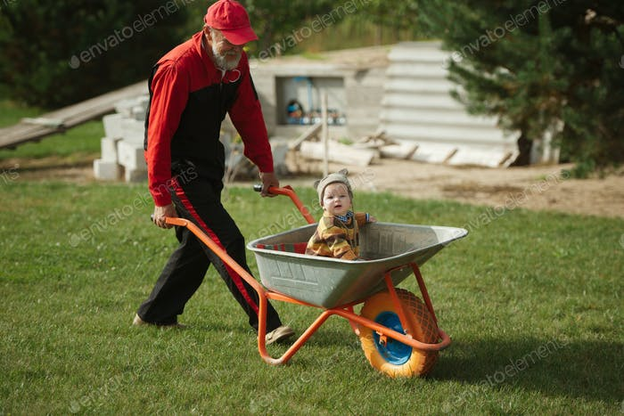 cute little boy sitting in wheelbarrow