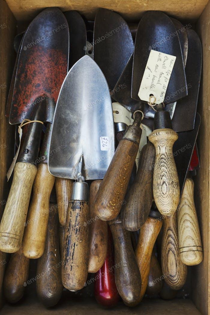 Overhead-Ansicht einer Sammlung von handgeführten Gartengabeln, mit Metallzinken und glatten Holzgriffen.