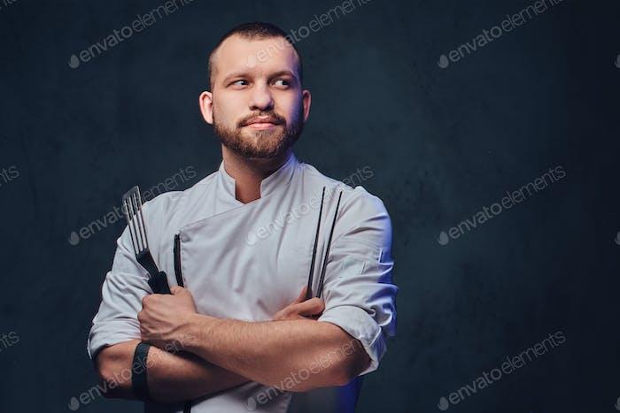 Chef cocinero sostiene un cuchillo sobre fondo gris oscuro.