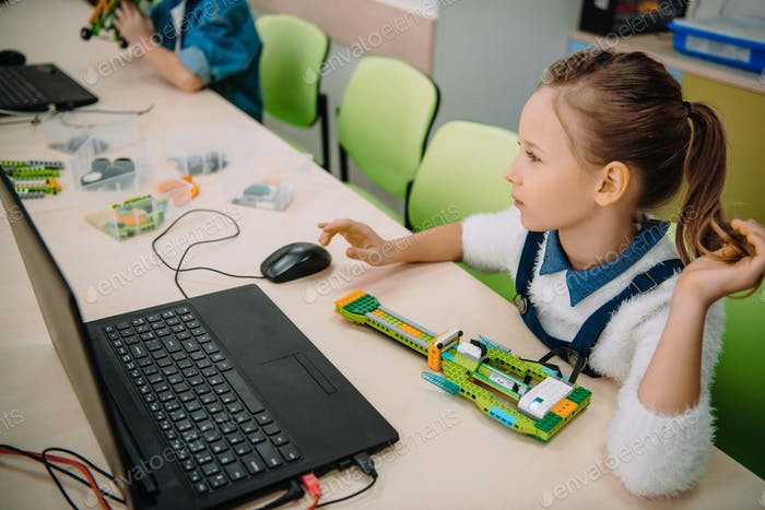 focused schoolgirl working with computer at machinery class