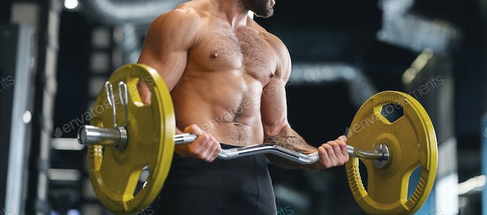 Muscular bodybuilder exercising with heavy barbell in gym
