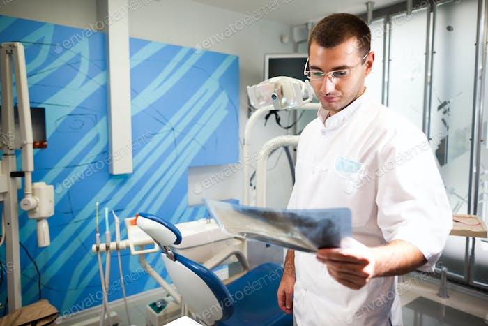 Junge Arzt Zahnarzt Mann in weißer Uniform und Brille stehend und Blick auf Zahnbild in