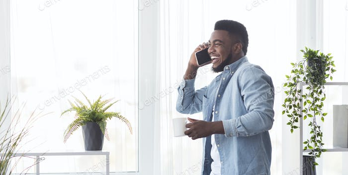Young cheerful businessman talking on phone and holding coffee cup