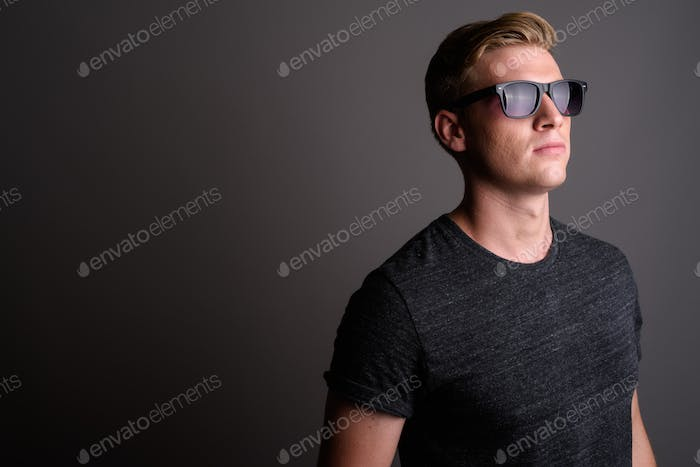 Young handsome man with blond hair wearing gray shirt against gr