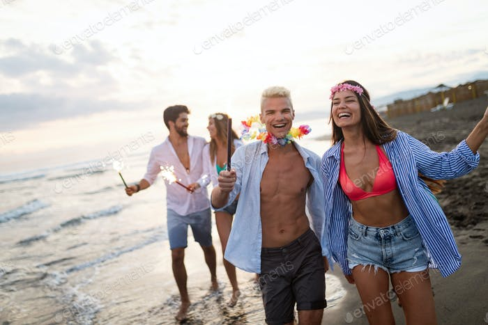 Happy friends having fun beach party outdoor with fireworks