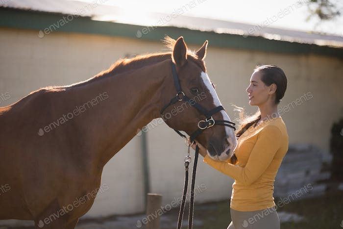 Female jockey with horse at barn