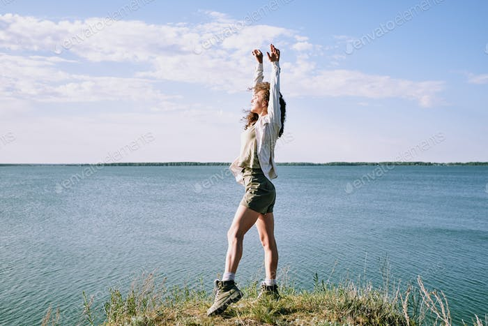 Young ecstatic woman with her arms raised standing on riverbank by water