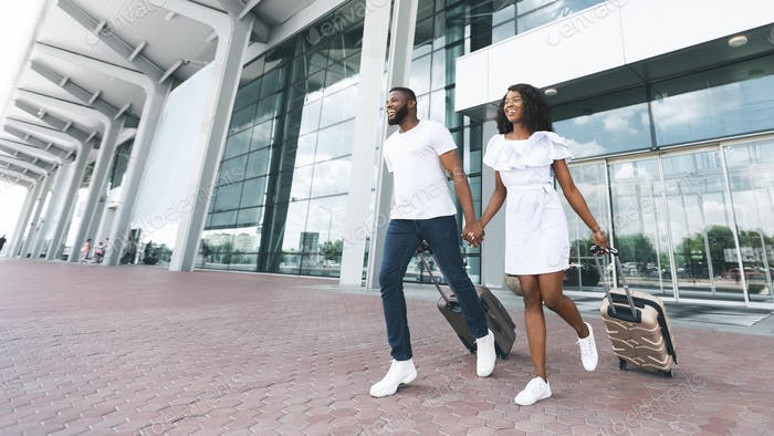 Happy african american couple running with luggage at airport exterior