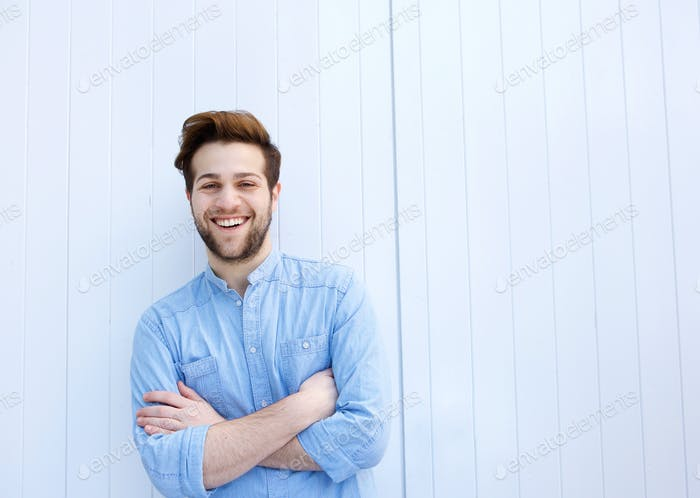 Attractive young man smiling with arms crossed