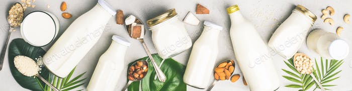 Various bottles of milk on grey concrete background