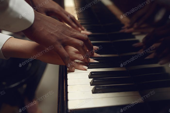 Black grand piano player hands on the keys