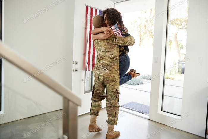 Returning millennial black soldier lifting his wife off her feet in the doorway of their home