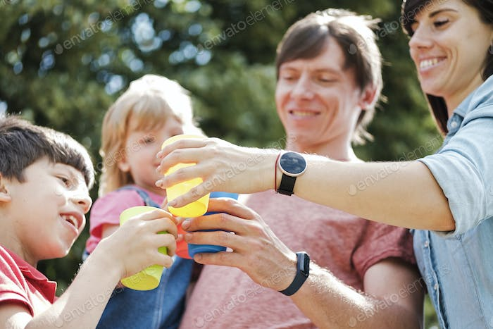 Happy young family toasting each other outdoors