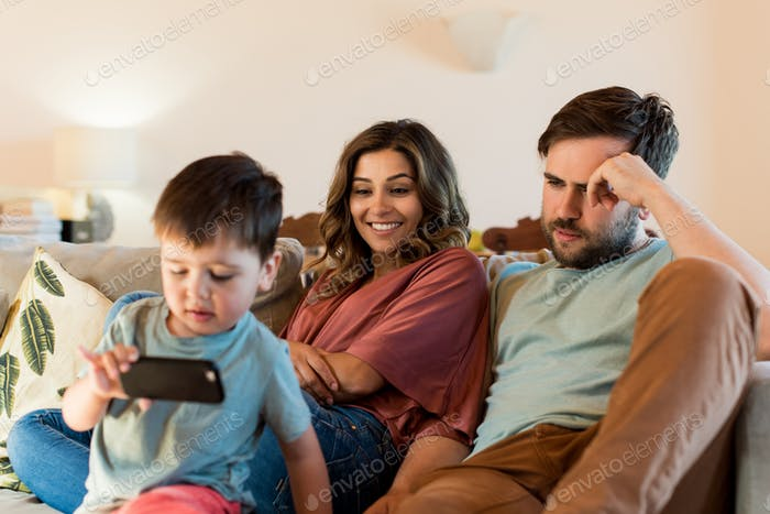 Happy couple and little boy with a smartphone at home
