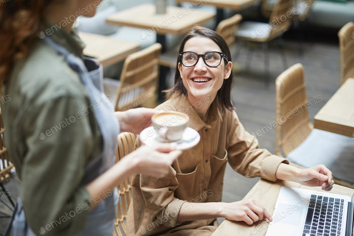 Young Businesswoman Ordering Coffee in Cafe