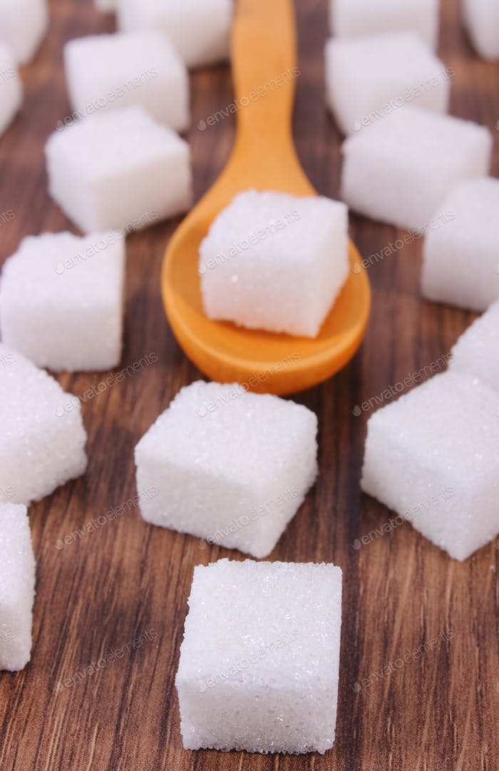 Wooden spoon with cubes of sugar on wooden background
