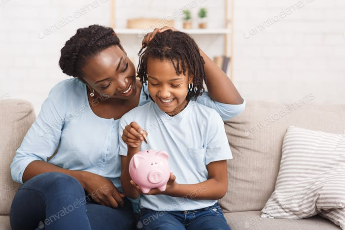 Little black girl putting money to piggy bank