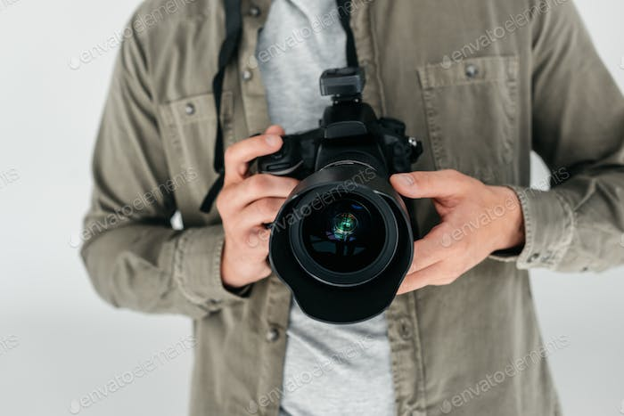 cropped view of professional male photographer with digital photo camera in photo studio, isolated