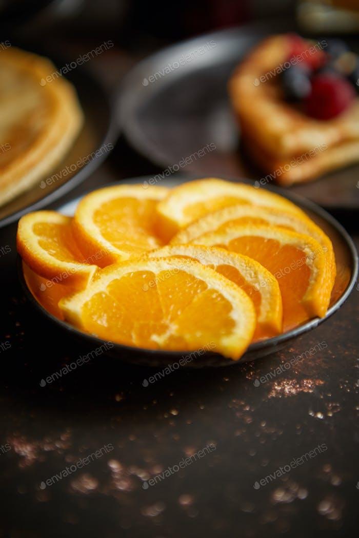 Close up on fresh orange slices placed on ceramic saucer