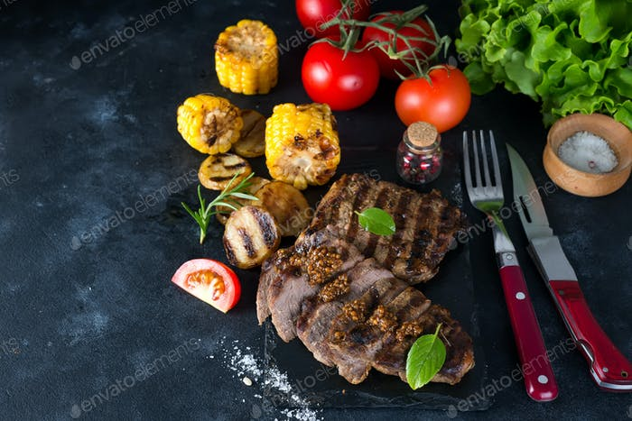 Grilled pork steak and vegetable , baked potatoes and corn on dark background