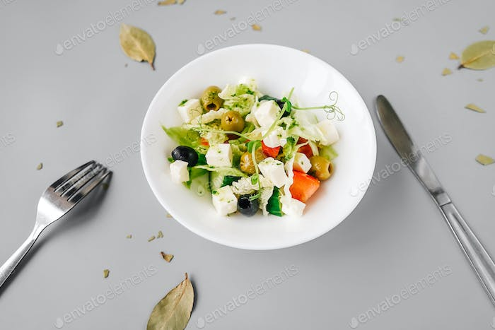Greek salad on gray background. Front view.