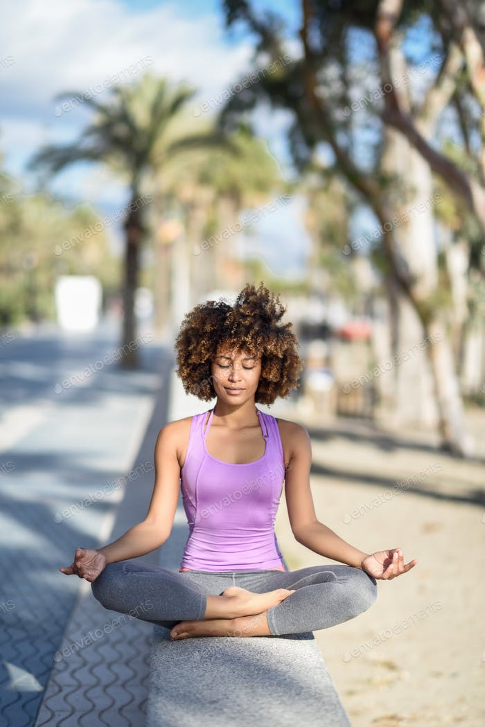 Black woman, afro hairstyle, in lotus pose with eyes closed in t