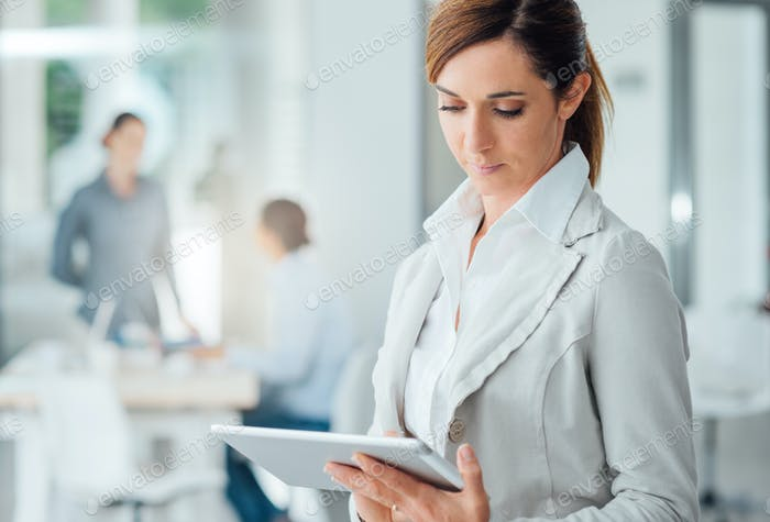 Professional business woman using a digital tablet