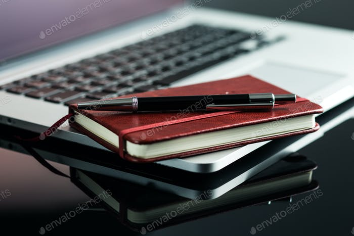 Laptop and diary with pen.