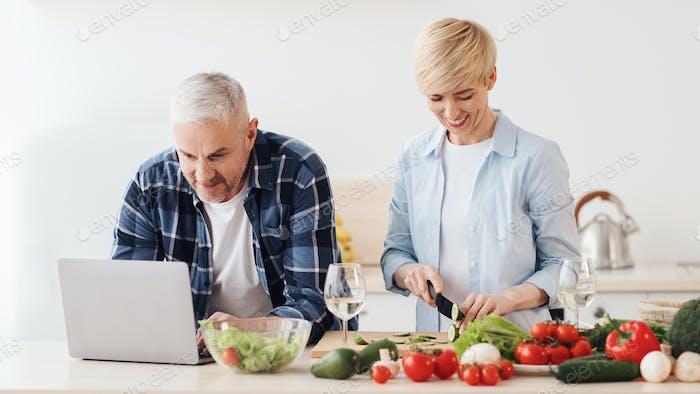 Glückliches Paar mittleren Alters 50er Jahre mit Laptop, bereitet gesundes Essen zu