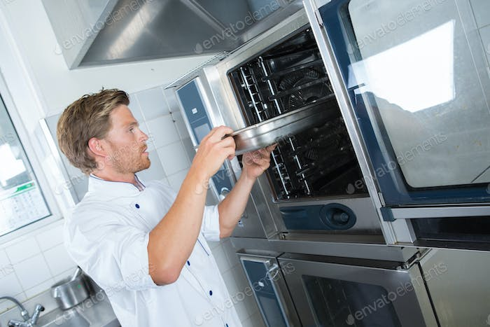 Chef taking tray from oven