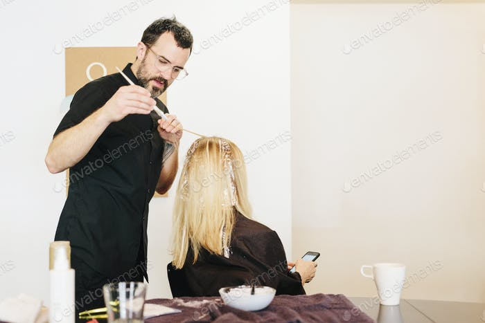 A hair colourist working with foils