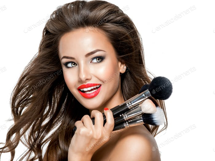 Beautiful happy expressive young woman holds the makeup brushes.