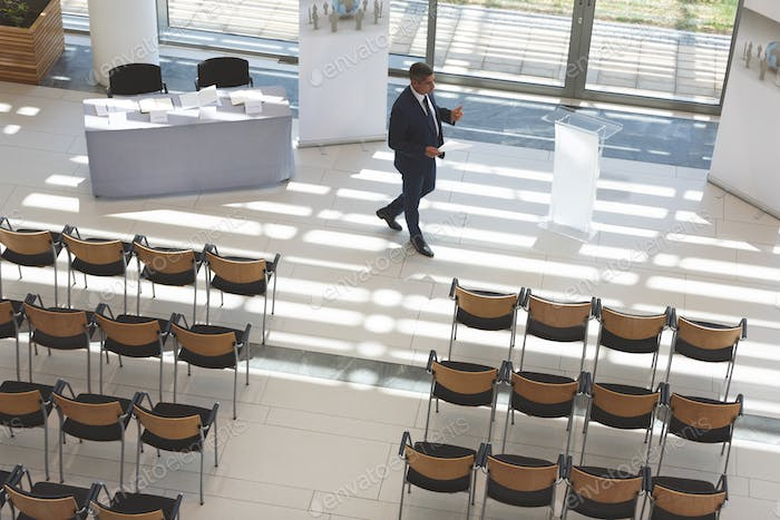 High angle view of mixed race businessman practising speech in empty conference room in office