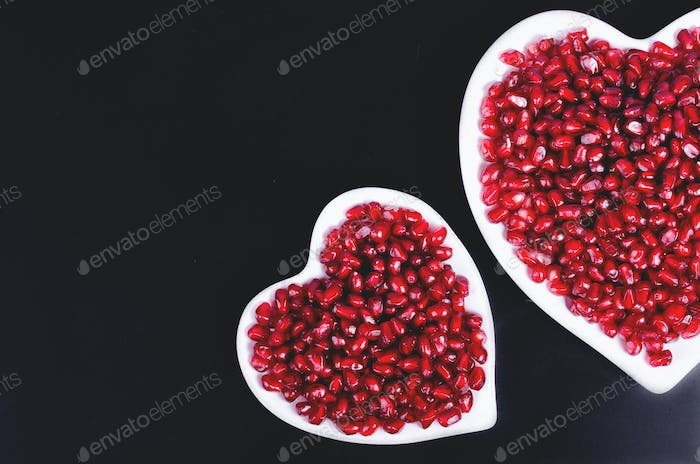 Two white heart shaped plates full of fresh juicy pomegranate seeds, little spoon, whole fruit and